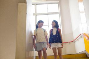 階段を歩く小学生女子2人の写真素材 [FYI01737790]