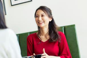 カフェで会話をする笑顔の30代女性の写真素材 [FYI01737798]
