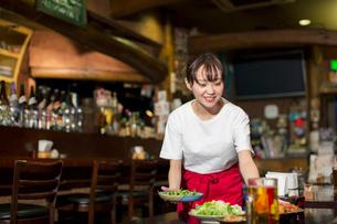 料理を運ぶ笑顔の居酒屋店員の写真素材 [FYI01737803]