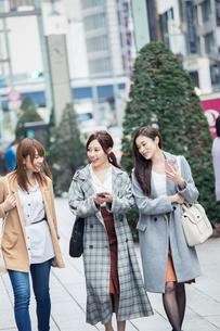 スマホを持ち街を歩く20代女性3人の写真素材 [FYI01737807]