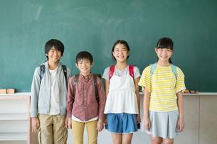 黒板の前に立つ小学生男女4人の写真素材 [FYI01737808]