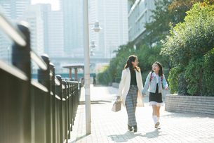 街を歩く笑顔の親子の写真素材 [FYI01737813]