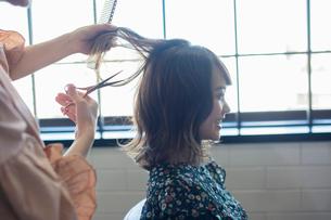 美容室でカットをしてもらう笑顔の20代女性の写真素材 [FYI01737841]