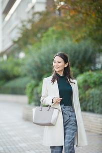 ビル街を歩く笑顔の30代女性の写真素材 [FYI01737845]