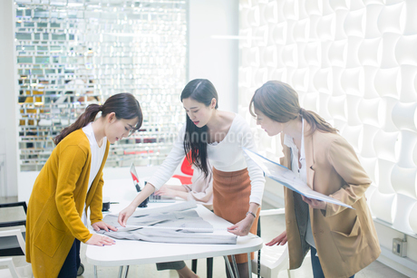 服の採寸をする20代女性3人の写真素材 [FYI01737846]