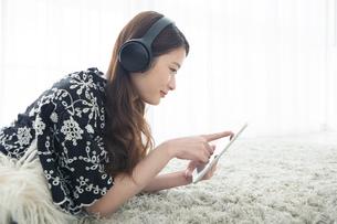 部屋でタブレットを操作する20代女性の写真素材 [FYI01737882]
