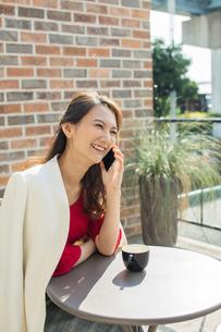 テラス席で通話をする30代女性の写真素材 [FYI01737886]