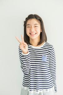 ピースサインをする笑顔の小学生女子ポートレートの写真素材 [FYI01737909]