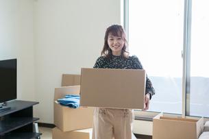 梱包したダンボールを運ぶ20代女性の写真素材 [FYI01737928]