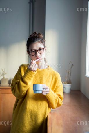 窓際で歯磨きをする20代女性の写真素材 [FYI01737936]