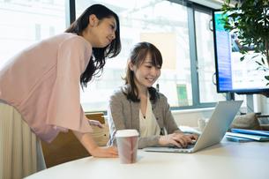 パソコンを覗き笑顔で話す女性2人の写真素材 [FYI01737963]