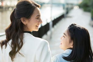街を歩く笑顔の親子の写真素材 [FYI01738011]