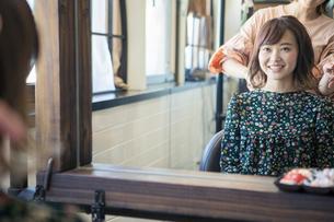 美容室でカウンセリング中の笑顔の20代女性の写真素材 [FYI01738056]
