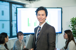 オフィスワーク中の笑顔の20代サラリーマンのポートレートの写真素材 [FYI01738064]