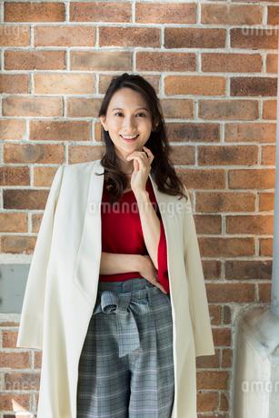 レンガの壁の前に立つ笑顔の30代女性の写真素材 [FYI01738096]