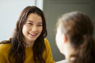 話を聞く笑顔の20代女性の写真素材 [FYI01738099]