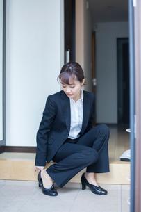 玄関で靴を履くスーツ姿の20代女性の写真素材 [FYI01738100]
