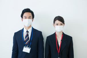 マスクをつけるスーツ姿の20代男女の写真素材 [FYI01738165]