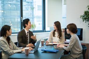 オフィスワーク中に笑顔で話す男女の写真素材 [FYI01738186]
