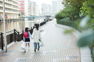 買い物帰りの親子の後ろ姿の写真素材 [FYI01738187]