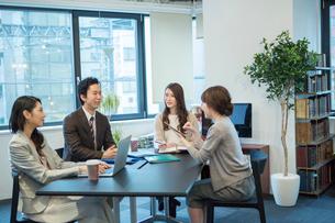 オフィスワーク中に笑顔で話す男女の写真素材 [FYI01738209]