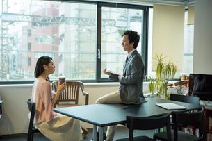 窓際で話すオフィスワーク中の男女の写真素材 [FYI01738216]