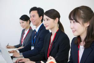 スーツを着て横並びに座る笑顔の男女の写真素材 [FYI01738238]