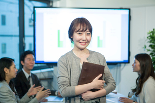 オフィスワーク中の笑顔の20代OLのポートレートの写真素材 [FYI01738242]