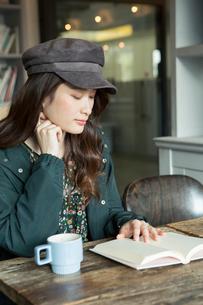 読書をする笑顔の20代女性の写真素材 [FYI01738244]