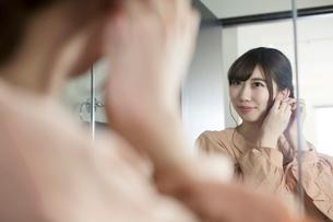鏡の前でピアスをつける20代女性の写真素材 [FYI01738264]