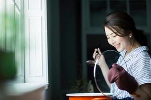 鍋料理を作る20代女性の写真素材 [FYI01738265]