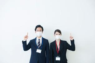 マスクをつけて指差しをするスーツ姿の20代男女の写真素材 [FYI01738271]