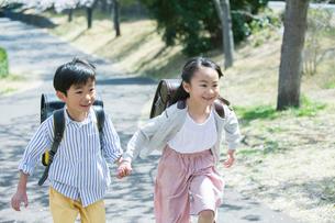 道を歩く笑顔の小学生男女の写真素材 [FYI01738305]