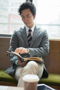 窓際に座りスケジュールを確認する20代男性の写真素材 [FYI01738338]