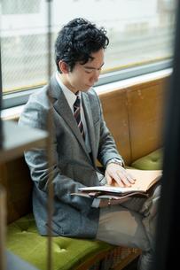 窓際に座りスケジュールを確認する20代男性の写真素材 [FYI01738355]