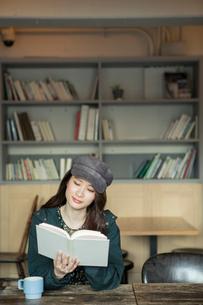 読書をする笑顔の20代女性の写真素材 [FYI01738361]