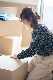ダンボールに梱包する20代女性の写真素材 [FYI01738402]