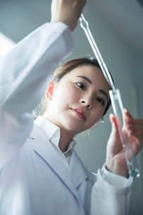 スポイトを使い試験管に液体を入れる20代研究員の写真素材 [FYI01738408]
