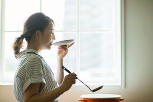 料理の味見をする20代女性の横顔の写真素材 [FYI01738416]
