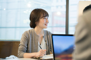 話を聞く笑顔の20代女性の仕事風景の写真素材 [FYI01738431]