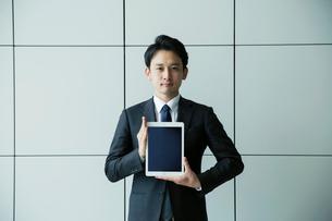 タブレットを持つスーツ姿の20代男性の写真素材 [FYI01738452]