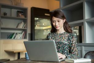カフェでパソコンを使う20代女性の写真素材 [FYI01738455]
