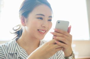 スマホを持つ笑顔の20代女性の写真素材 [FYI01738457]