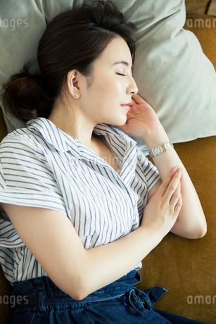 ソファに寝転がりうたた寝をする20代女性の写真素材 [FYI01738467]