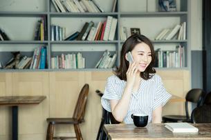 カフェで電話をする笑顔の20代女性の写真素材 [FYI01738469]