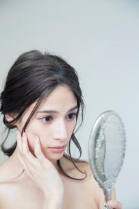 鏡を持ち肌に手を当て状態を確かめる20代女性の写真素材 [FYI01738471]
