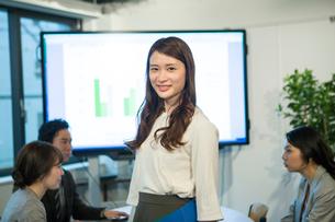 オフィスワーク中の笑顔の20代OLのポートレートの写真素材 [FYI01738490]