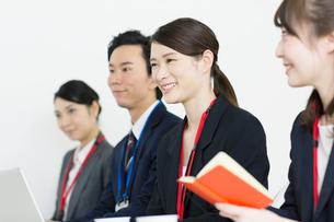 スーツを着て横並びに座る笑顔の男女の写真素材 [FYI01738496]