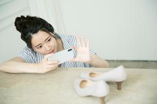 靴の写メを撮る20代女性の写真素材 [FYI01738523]