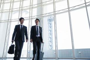 屋内を歩くスーツ姿の男性2人の写真素材 [FYI01738535]